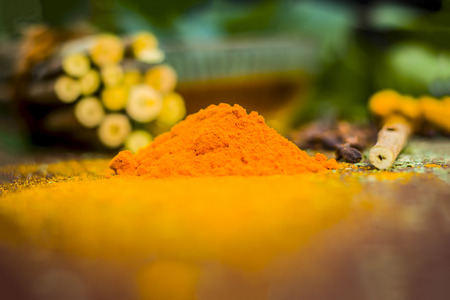 Powder of Indian lilac,Azadirachta indica in a glass plate with its leaves and raw underpowered turmeric.