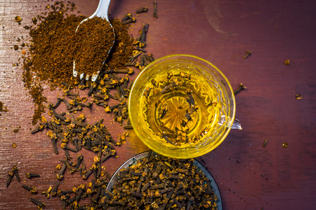 Tea of clove,Syzygium aromaticum with powder of clove and raw clove on a wooden surface.
