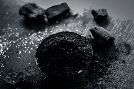 Powder of coal with raw coal on a wooden surface.