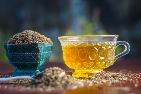 Black cumin seeds,shah jerra,Nigella sativa  and its tea on brown wooden surface.;