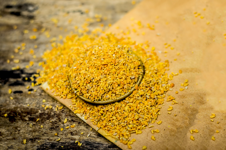 Crushed Fenugreek seeds,Trigonella foenum-graecum seeds,methi ke koriya in a bowl on wooden surface. Stock Photo