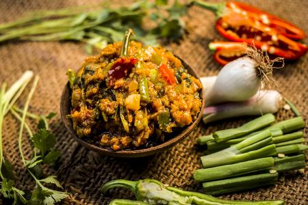 Close up of Indian Dish eaten in winter season Baingan ka Bharta with vegetables like:Spring onions,Allium fistulosum,Coriander,Coriandrum sativum,Garlic,Allium sativum and chills.