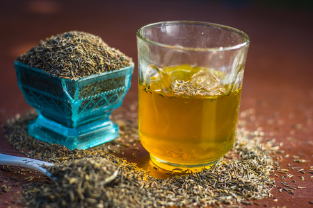 Black cumin seeds,shah jerra,Nigella sativa  and its extracted water in a transparent glass on brown wooden surface.;