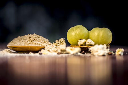 Raw fresh ripe Phyllanthus emblica,amla or Indian gooseberry with its powder on wooden surface. Stock Photo