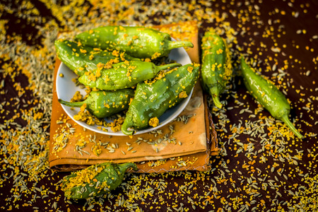 Green chilli pickle marinated in mustard seeds and mustard oil. Dark gothic style still life concept.