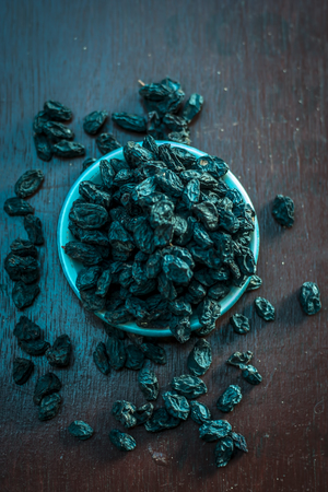 Black raisin or kali kishmish or Zante currant in a white plate on wooden surface in dark Gothic colors to decreases the chance of Dehydration.