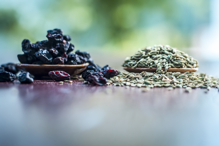 Raw dried fennel with black raisin a ayurvedic treatment to cure dehydration on wooden surface in dark Gothic colors.