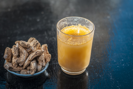 Dried ginger or Zingiber officinale or Soth,Sonth with ayurvedic medicinal extracted juice in a transparent glass on wooden surface improves the digestion and decreases the chances of cancer,diabetes. Reklamní fotografie