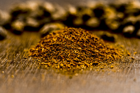 Raw black cardamom with its powder on a brownish wooden surface. 版權商用圖片