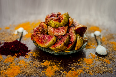 Close up of popular Indian guava pickle or jamrudh ka achar on a wooden surface with raw guava and all the necessary spices. Stockfoto