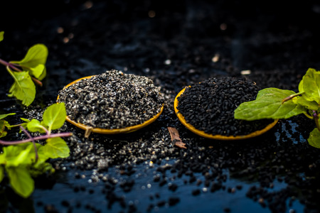 Close up of kalonji, Roman coriander, mint leaves, and powder of kalonji with its extracted oil for piles treatment, weight loss, healthy kidney, to low blood pressure etc. Stock Photo