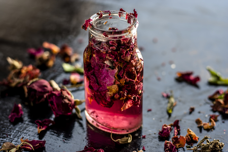 Close up of extracted rose water or gulab jal or gulab ka pani in a transparent bottle on black surface Stock Photo