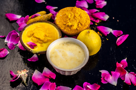 Chana,haldi,limbo & milk  ka ubtan or ayurvedic face pack of Turmeric, Lemon,gram flour & milk on wooden surface for good skin and no black heads or any skin related problems. Stock Photo