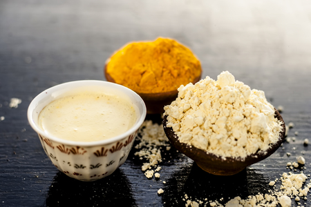 Chana,haldi,limbo ka ubtan or ayurvedic face pack of Turmeric, Lemon, and gram flour on wooden surface for good skin and no acnes or pimples. Stock Photo