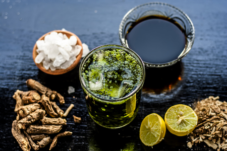 Sharbat or Indian styled water beverage of Nannari or Indian sarsaparilla with all its ingredients i.e. Nannari syrup,water,ice cubes, lemon juice and sweet basil on wooden surface.