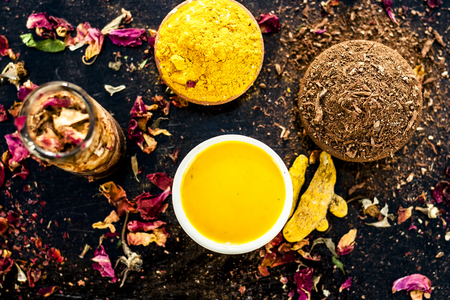 Ayurvedic face pack of chandan,Haldi, and gulab jal or gulab ka pani, with raw turmeric, sandal wood powder and rose petals on wooden surface for good and natural bright, white skin.