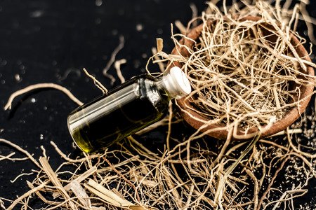 Floral and ayurvedic essence of herb Vetiver grass or Khus in a transparent bottle used in many beverages of Indian and Asia with dried vetiver grass in a clay bowl on black surface.;
