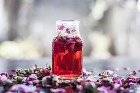 Rose water or Gulab jal or Gulab ka pani or Rosa water in a bottle on wooden surface with rose petals.