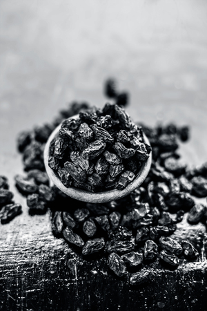 Organic dry fruit dried black grapes or black raisins or kali kishmish or black currant in a clay bowl on wooden surface.