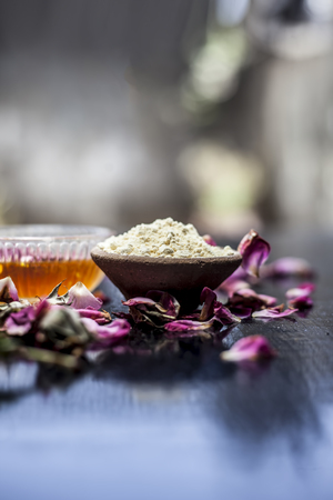 Herbal face pack of gram flour and honey with some rose petals on wooden surface.