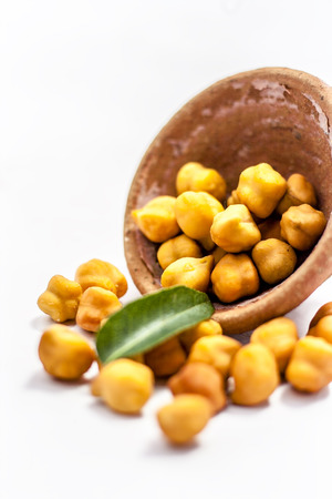 Raw bright dark brown colored Desi chana or original chickpea in a glass bowl isolated on white. Stock Photo