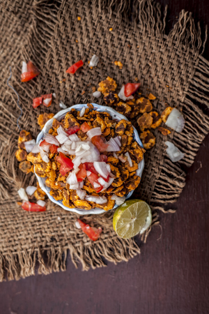 Popular Indian & Asian snack or junk food chana chur garam in a clay bowl on wooden surface with onions,lemon and tomatoes.