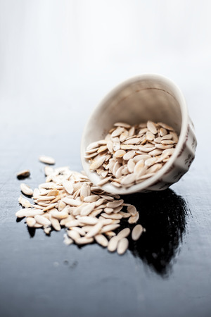 Edible dried raw organic seeds of musk melon or cantaloupe or tati or honeydew on a wooden surface.
