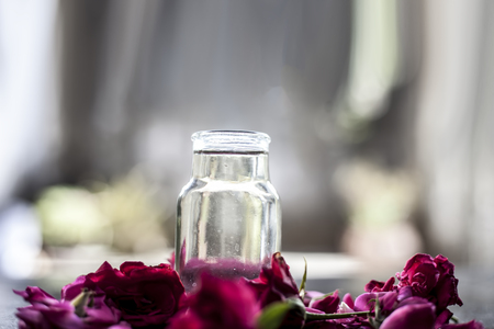 Medicinal and floral essence of Rose or gulab popularly known as gulab jal or gulab ka pani in Asia with fresh bright rose petals on wooden surface.