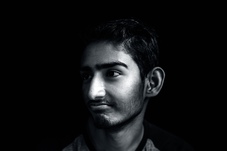 Portrait of a young Asian Indian sad about the exam result or not getting pocket money posing in black background.Low key portrait.