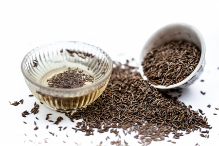 Common cumin or zeera or jeera in a bowl isolated on white with its extracted water in a bowl.