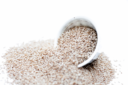 Sesame seeds or or white sesame seeds or tel or til or tal in a bowl isolated on white.