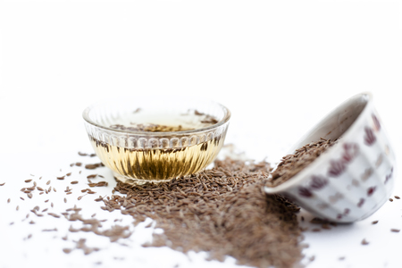 Common cumin or zeera or jeera in a bowl isolated on white with its extracted water in a bowl.;