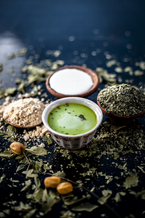 Mulpani mitti ubtan with all its ingredients i.e. Neem or Indian lilac, and milk on wooden surface used to remove the black heads and acne and pimples.