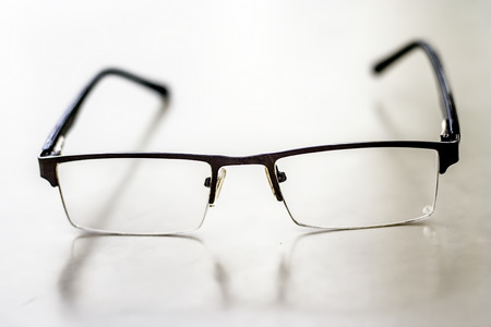Black colored half frame rim reading glasses or spectacles to cure eye disease myopia.