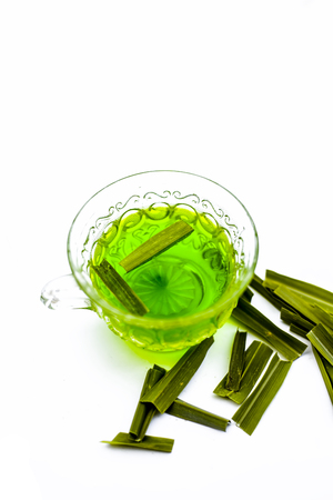 Green colored tea of lemon grass in a transparent cup isolated on white used in many ayurvedic treatments.