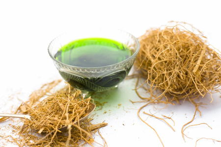 Close up of dark green colored herbal syrup of Khus or vetiver grass isolated on white in a transparent glass used to in various flavored beverages.