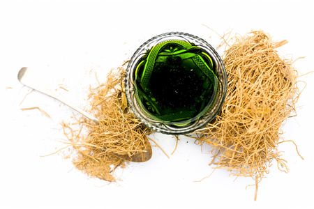 Dark green colored Khus or vetiver grass's extracted syrup isolated on white with some dried vetiver grass used in Indian and Asian summer drinks as well as cold drinks.