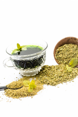 Raw fennel with its powder and its beneficial tea or extract in a transparent cup isolated on white.