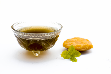 Jaggery or gud with its syrup in a transparent bowl isolated on white.