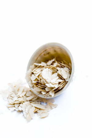 Close up of Flattened rice or beaten rice or Phoa or pava in a bowl isolated on white.