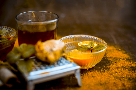 Close up of Ayurvedic home remedy for common cold: Fresh organic ginger ( grated) , warm water, cinnamon stick, honey, and lemon juice.