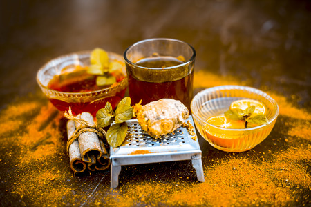 Ancient ayurveidc home remedy for common cold: Grated ginger, warm water, cinnamon powder, honey, and lemon juice in a transparent glass on wooden surface.