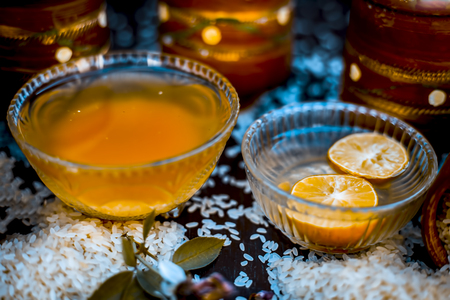 Close up of effective remedy for white heads and pimples: Rice water and lemon juice in a transparent glass bowl on wooden surface with raw rice in a clay vessel. Stock Photo