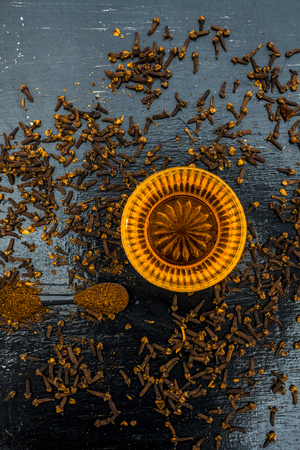 Herbal and ayurvedic treatment or remedy for asthma: Dry cloves with honey on wooden surface.