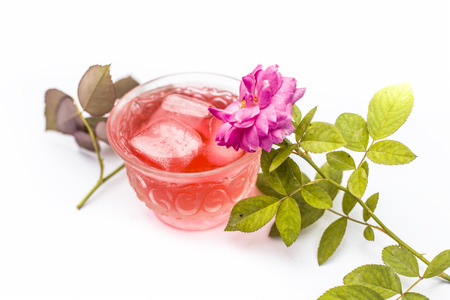 Close up of Iced rose tea or iced rosa tea  in transparent cup isolated on white with some Rosaceae petals in surroundings.