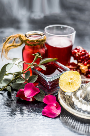Close up of herbal face pack of pomegranate and lemon juice with rose water on wooden surface with some sliced lemons and pomegranates used for Dull skin.