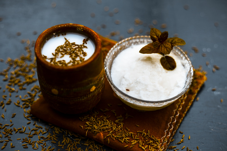 Traditional summer drink i.e. is most popular in Asia and India i.e. Chas or chaas or buttermilk or chhaachh in a clay glass with curd and coriander powder and salt on wooden surface,Close up.
