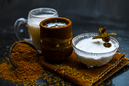 Traditional summer drink i.e. is most popular in Asia and India i.e. Chas or chaas or buttermilk or chhaachh in a clay glass with curd and coriander powder and salt on wooden surface,Close up. Standard-Bild