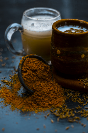 Traditional summer drink i.e. is most popular in Asia and India i.e. Chas or chaas or buttermilk or chhaachh in a clay glass with curd and coriander powder and salt on wooden surface,Close up. Stock Photo