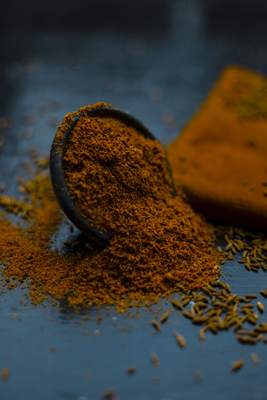 Close up of powdered cumin or zeera or jeera with raw cumin on wooden surface in a clay bowl on a cloth or napkin.